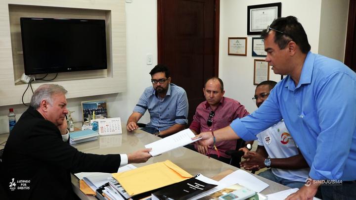 O desembargador Fróz Sobrinho recebendo cópia de requerimento das mãos do presidente do Sindjus-MA, Aníbal Lins; os demais sentados são o diretor de Mobilização do Sindicato, Pedro Davi Araújo, membro do Conselho de Ética, Anísio Júnior; e o vice-presidente, George Ferreira