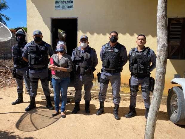 oficiala Sara Monteiro ladeada pelos policiais que a acompanharam para o cumprimento da decisão judicial